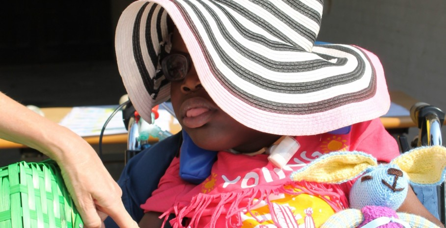 young girl with ventilator wearing summer hat